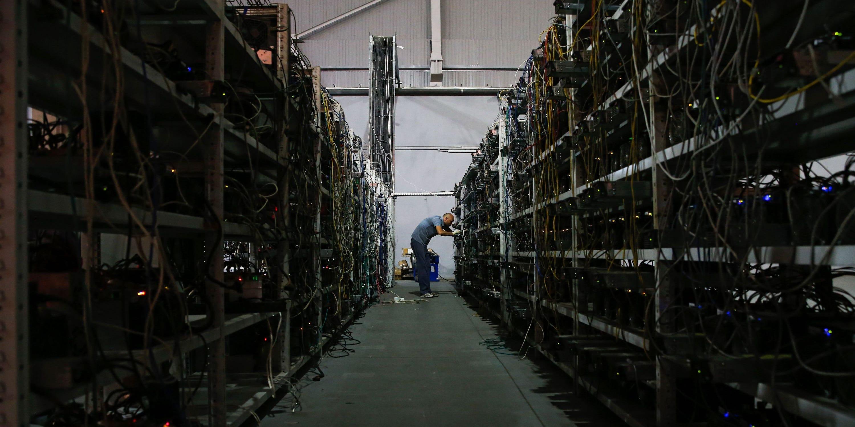 Un uomo si trova alla fine di un lungo corridoio. Le pareti sono piene di computer e cavi, che vengono utilizzati per estrarre bitcoin.